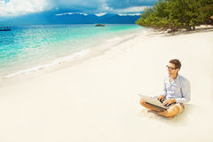 Man with laptop on colorful beach. Of island Royalty Free Stock Photography
