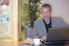 Man with laptop computer by coffee cup, portrait Royalty Free Stock Photos