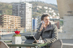 Man laptop computer and talking by phone in public space. stock photo