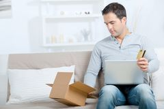 Man with laptop credit card and cardboard boxes at home stock photography