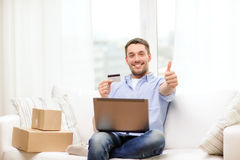 Man with laptop, credit card and cardboard boxes Stock Images