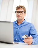 Man with laptop and credit card at home Stock Images