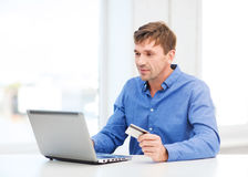 Man with laptop and credit card at home Royalty Free Stock Images