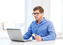 Man with laptop and credit card at home stock image