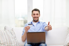 Man with laptop and credit card showing thumbs up Stock Photography