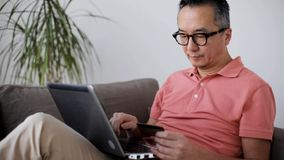 Man with laptop and credit card on sofa at home stock video footage