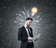 Man with laptop, exclamation marks, light bulb Royalty Free Stock Images