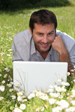 Man on laptop in field Royalty Free Stock Image