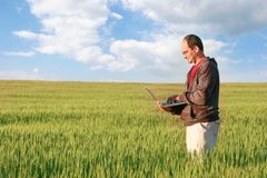 Man with laptop in field. Man with laptop in green field Royalty Free Stock Photography