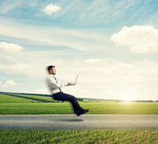 Man with laptop flying over the road Royalty Free Stock Photo