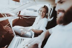 Man With Laptop. Girl With Headphones. Tesla Car. Man Works With Laptop. Girl In Headphones. Tesla Car. Front Seat. Innovation Technology. New Generation Electro royalty free stock photo