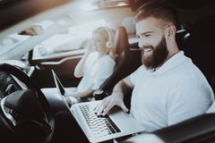Man With Laptop. Girl With Headphones. Tesla Car. Man Works With Laptop. Girl In Headphones. Tesla Car. Front Seat. Innovation Technology. New Generation royalty free stock photography