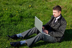 Man with a laptop on the grass. Young man with a laptop on the green grass Royalty Free Stock Images