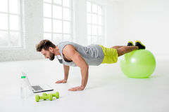 Man with laptop in the gym. Man watching online trainig with laptop training on the fitball in the gym Stock Images