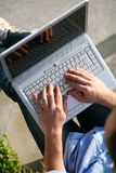 Man with laptop hands on keyboard. Working outdoors royalty free stock image