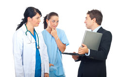 Man with laptop having conversation with doctors. Man holding a laptop and  having conversation with  two doctors women isolated on white background Royalty Free Stock Photography
