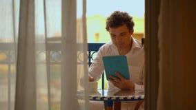 Man with laptop having tea on the balcony stock video