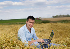 Man with laptop on haystack Stock Image