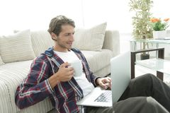 Young man with laptop holding a cup sitting on the floor near the sofa Stock Photo