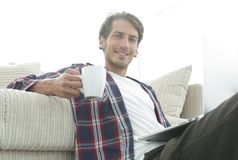 Young man with laptop holding a cup sitting on the floor near the sofa Royalty Free Stock Photos