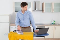 Man With Laptop While Ironing Cloth Stock Photography