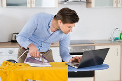 Man With Laptop While Ironing Cloth Royalty Free Stock Photography