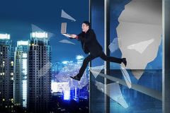 Man with laptop jump through office building window Royalty Free Stock Photos