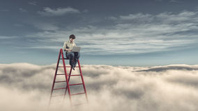 Man with a laptop on a ladder above the clouds Royalty Free Stock Image