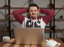 Man with laptop leans back Stock Images