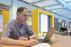Man with laptop in a library Stock Images