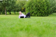 Man with laptop lying on green grass Stock Photo