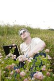 Man with laptop on meadow Stock Photo