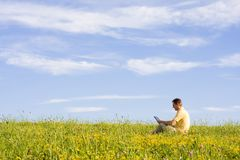 Man with laptop on meadow. Man working with laptop in a meadow of flowers Royalty Free Stock Photo