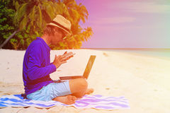 Man with laptop and mobile phone on tropical beach Royalty Free Stock Photos