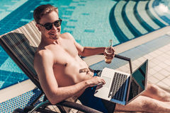 Man with laptop near swimming pool stock images