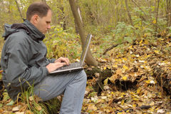Man with laptop outdoor. Man working on the laptop at the autumn forest. Man is sitting on the fall tree with yellow leaves and moss Stock Photos