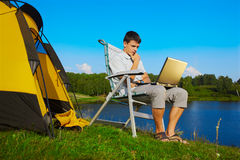 Man with laptop outdoor. Expression portrait of thoughtful man with laptop sitting in folding chair near camp tent outdoors Royalty Free Stock Photography