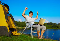 Man with laptop outdoor. Expression portrait of succesful man with laptop sitting in folding chair near camp tent outdoors Royalty Free Stock Images