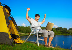Man with laptop outdoor. Expression portrait of succesful man with laptop sitting in folding chair near camp tent outdoors Stock Image