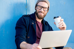 Man with laptop outdoors. Stylish man dressed casual in sweater and hat working with laptop sitting with coffee near the blue wall background Royalty Free Stock Photos