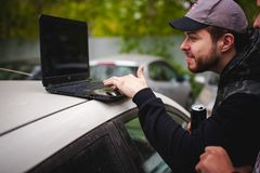 Man with a laptop in parking lot in yard near car is doing manipulations with cyber system, concept. Stock Image
