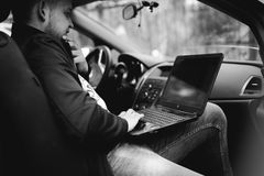 Man with a laptop in parking lot in yard near car is doing manipulations with cyber system, concept. Stock Photo