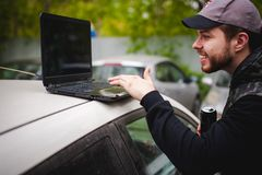 Man with a laptop in parking lot in yard near car is doing manipulations with cyber system, concept. Royalty Free Stock Image