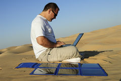 Man with laptop and portable solar charger Stock Photography