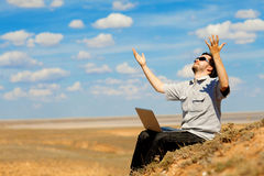 Man with laptop praying to the God. Outdoors Royalty Free Stock Photography