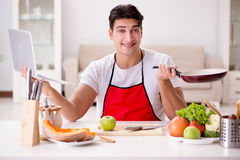 The man with laptop preparing food at the kitchen Stock Photography