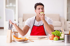 The man with laptop preparing food at the kitchen Stock Images