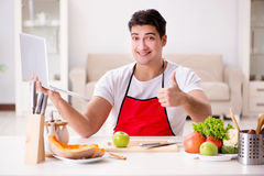 The man with laptop preparing food at the kitchen Royalty Free Stock Image