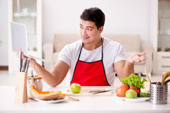 The man with laptop preparing food at the kitchen Stock Photos