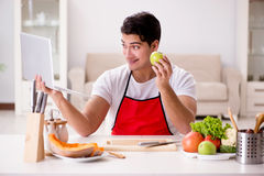 The man with laptop preparing food at the kitchen Royalty Free Stock Images